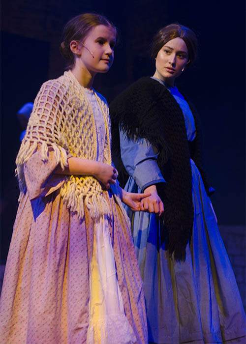 Jane Eyre in her period Victorian costume a blue dress with a stole