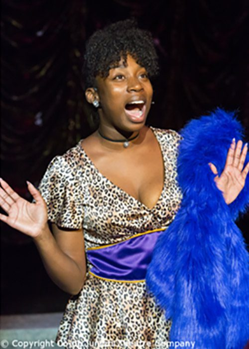 Deloris Van Cartier in leopard skin short dress with blue fake fur costume. Scene from Sister Act the Musical.